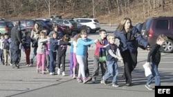 Fotografía cedida que muestra a unos agentes de policía evacuando a unos niños de la escuela Sandy Hook en Newtown, Connecticut.