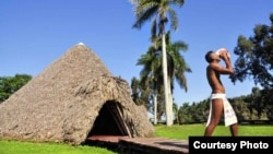"""""""Taíno"""" en la """"aldea"""" Guamá soplando en un cobo o caracol (fotuto en lengua taína)."""