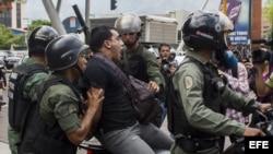 Miembros de la Guardia Nacional Bolivariana detienen a un manifestante durante una marcha de opositores.