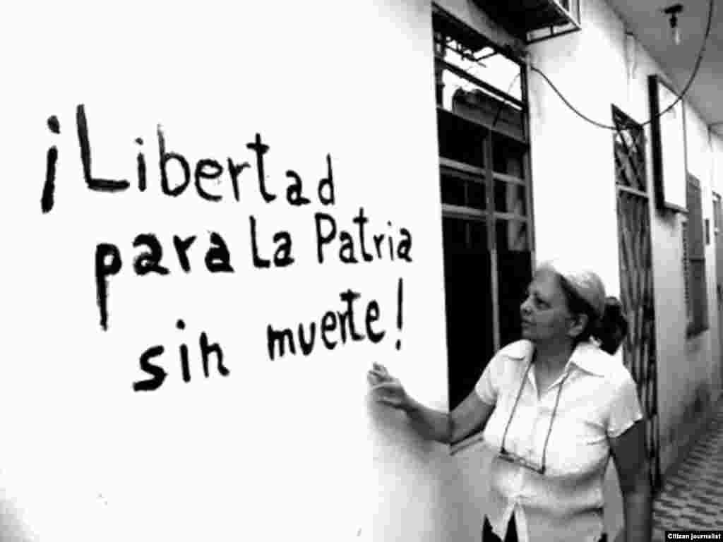 La disidente Martha Beatriz Roque mostrando una pintada en su casa. Actualmente preside la Red Cubana de Comunicadores Comunitarios.