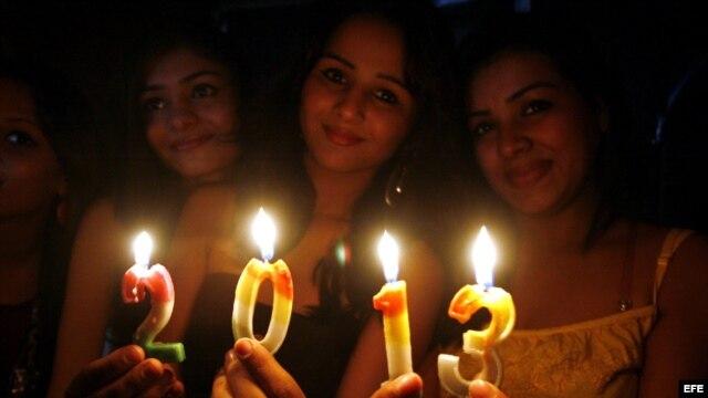 Jóvenes sostienen velas con el número 2013 durante las celebraciones del nuevo año en Bhopal (India).