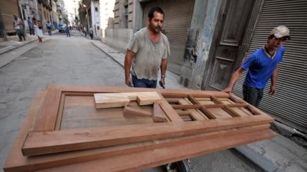 Un carpintero carga varias puertas en una carretilla en La Habana (Cuba).