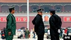 Archivo - Policías vigilan las entradas y salidas en la plaza de Tiananmen, en Pekín, China.