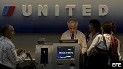 Pasajeros facturan para su vuelo en un mostrador de United Airlines.