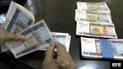 Una persona cuenta pesos cubanos convertibles.