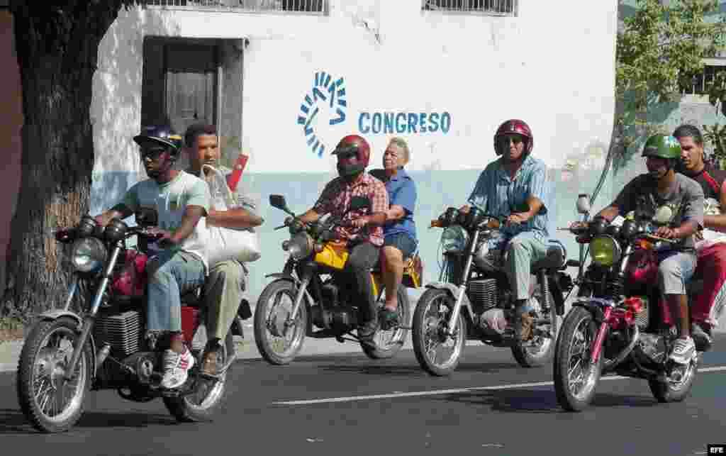 Varias personas viajan en moto-taxi particulares por las calles de Santiago de Cuba.