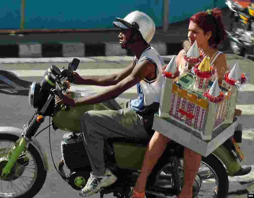 Una mujer viaja en una moto-taxi particular por las calles de Santiago de Cuba.