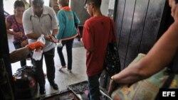 Viajeros pasan por un control sanitario en la terminal de ómnibus en La Habana tras informarse de casos de cólera.