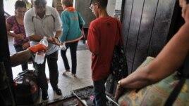 Varias personas pasan por un control sanitario en la terminal de Ómnibus Nacionales en La Habana, Cuba, tras informarse de casos de cólera
