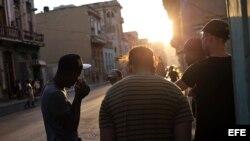 Varios jóvenes conversan en una esquina de La Habana.