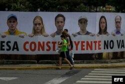 Transeúntes caminan frente a una valla en rechazo a la Asamblea Constituyente.