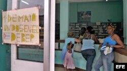Una mujer hace cola en una farmacia de La Habana junto a un cartel alusivo al Primero de Mayo.