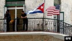 Dos jóvenes cubanos conversan junto a las banderas de Estados Unidos y Cuba.