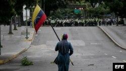 Un manifestante camina frente a efectivos de la Policía Nacional Bolivariana (PNB) el 7 de junio de 2017, en Caracas.