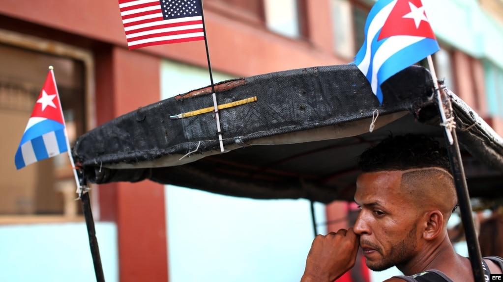 El conductor de un bicitaxi, adornado con banderas de Cuba y EEUU, espera la llegada de clientes en La Habana (Cuba).
