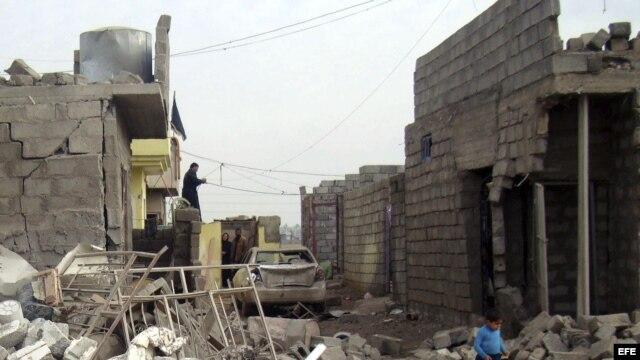 Un niño iraquí camina entre los escombros producidos por un ataque con coche bomba en pueblo de Tahraua, al este de Mosul, en Irak. Archivo.