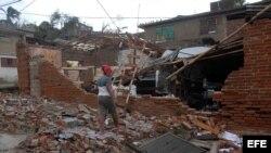 """Una mujer observa los destrozos ocasionados a su hogar por el paso del huracán """"Sandy"""" en la ciudad de Santiago de Cuba."""