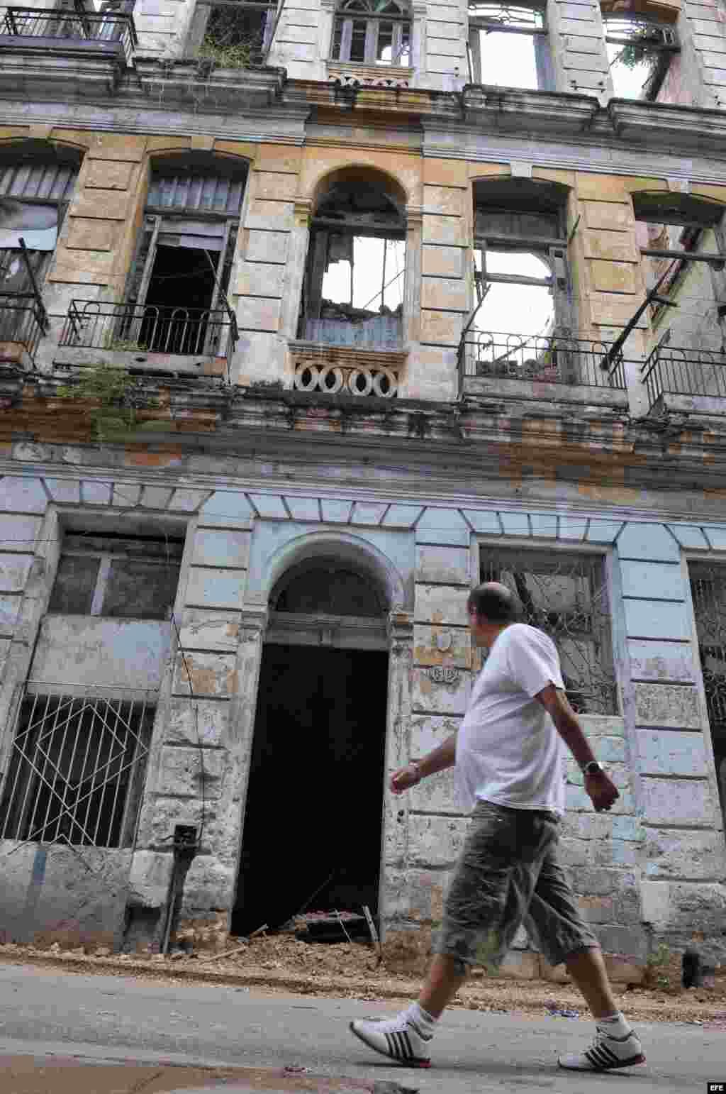 Un hombre camina frente a un edificio que se derrumbó parcialmente en Centro Habana