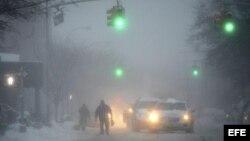 Peatones y vehículos circulan por las calles nevadas del distrito de Brooklyn en Nueva York (Estados Unidos).