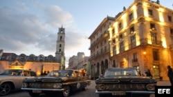 Varios autos clásicos permanecen parqueados en una plaza en La Habana Vieja.