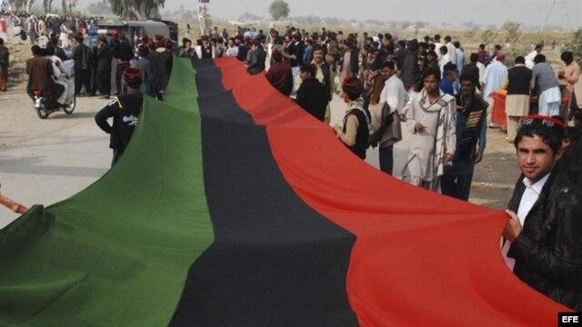 Simpatizantes del gobernante Partido Popular (PPP) portan una bandera del partido durante un acto para rendir tributo a la exprimera ministra paquistaní Benazir Bhutto con motivo de el quinto aniversario de su asesinato.