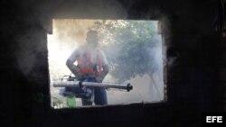 Un trabajador de la salud fumiga una casa para combatir el dengue