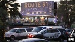 """Vehículos policiales bajo una señal que indica la localización del festival country """"Route 91 Harvest"""", en Las Vegas, lugar donde se produjo el tiroteo"""