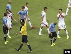 El árbitro alemán Félix Brych (c) saca la tarjeta roja al defensa uruguayo Maximiliano Pereira (d), tras cometer falta al delantero costarricense Joel Campbell.